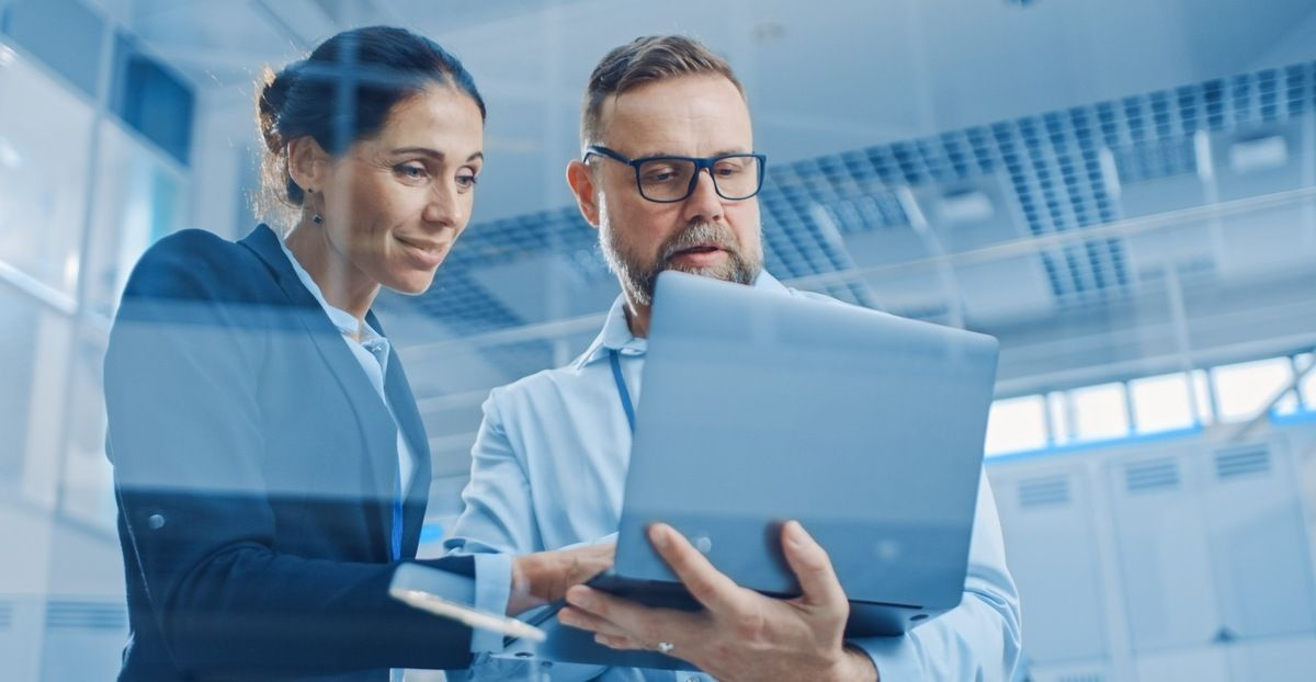 Mellomledere har en viktig rolle i lærende organisasjoner. Illustrasjon: mann og kvinne ser på laptop